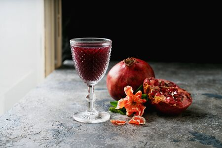 Pomegranate fruits, whole and half, Glass of pomegranate juice, decorated with pomegranate flowering branch near the window over rustic background. Side view. Close up. Selective focus Banque d'images
