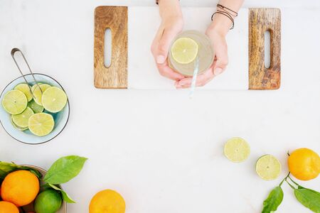 Citrus infused water preparation. Female hands holding the glass of citrus infused water. Slices of lime on the plate, fresh oranges and limes on the table. Top view. Banque d'images