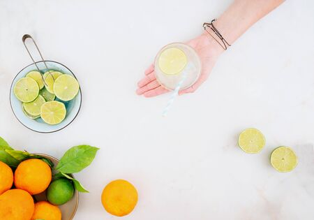 Citrus infused water preparation. Female hand holding the glass of citrus infused water. Slices of lime on the plate, fresh oranges and limes on the table. Top view.