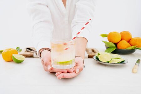 Citrus infused water preparation. Female hands holding the glass of citrus infused water with ice and straw. Slices of lime on the plate, fresh oranges and limes at background. Side view. Banque d'images