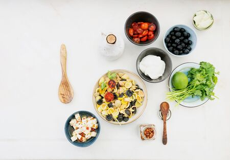 Add-ins for Pasta Salad. Traditional Italian salad dish. Orecchiette Arlecchino, roasted tomatoes, onion, black olives, lime, feta cheese, olive oil, spices and herbs. Top view.