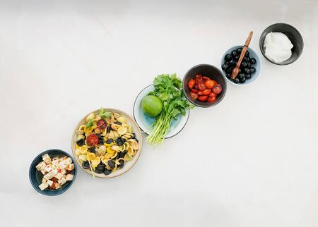 Add-ins for Pasta Salad lined up in a row. Traditional Italian salad dish. Orecchiette Arlecchino, roasted tomatoes, onion, black olives, lime, feta cheese, olive oil, spices and herbs. Top view Standard-Bild