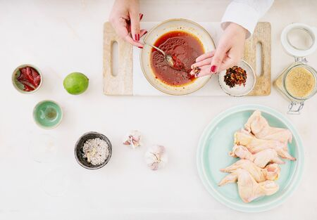 Raw chicken wings and ingredients for Korean marinade with gochuang paste, honey, garlic, soy sauce and spices. Cooking process. Chef whisking together add-ins for the marinade.