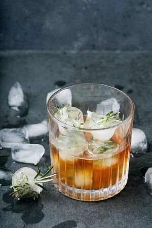 Misted glass of whiskey on the rocks served with frozen herbs in ice cubes over dark background. Selective focus. Standard-Bild