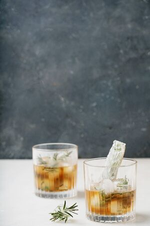 Misted glasses of whiskey on the rocks served with frozen herbs in ice cubes. Side view. Selective focus. Standard-Bild