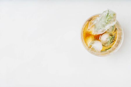 Single glass of whiskey on the rocks served with frozen herbs in ice cubes over the white background. Top view. Copy space Standard-Bild