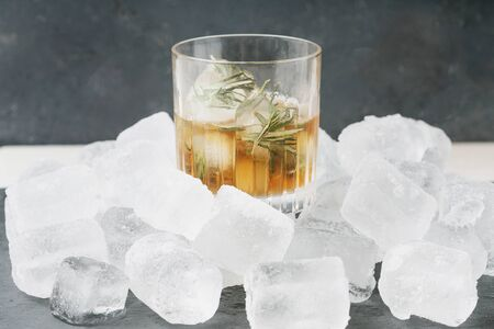 Misted glass of whiskey on the rocks served with frozen herbs in ice cubes over the ice heap. Side view. Selective focus.
