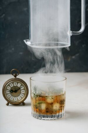 Whiskey o'clock. Process of serving a glass of whiskey on the rocks with a smoke. Lifting up a jug full of smoke over the glass and vintage clock. Side view. Selective focus. Standard-Bild