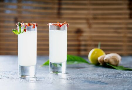 Ginger lemon shot. Immune boosting health defending drink. Bamboo background. Selective focus Standard-Bild