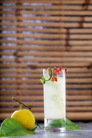 Ginger lemon shot with citrus on the branch. Immune boosting health defending drink. Bamboo background. Selective focus Standard-Bild