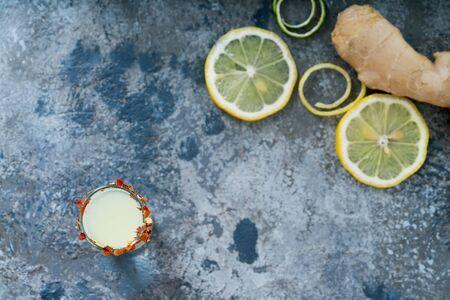 Ginger lemon shot, lemon slices and ginger. Immune boosting health defending drink. Rustic background. Top view. Selective focus
