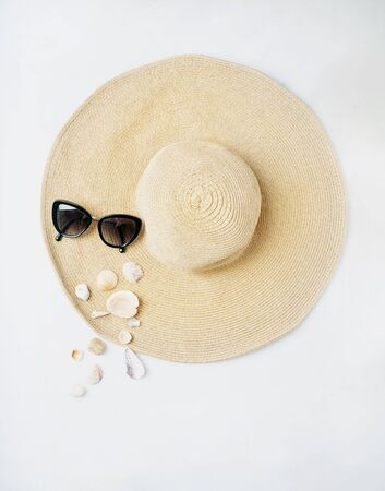 Summertime concept. Beach set: sunglasses and shells over summer hat on the white background. Top view.