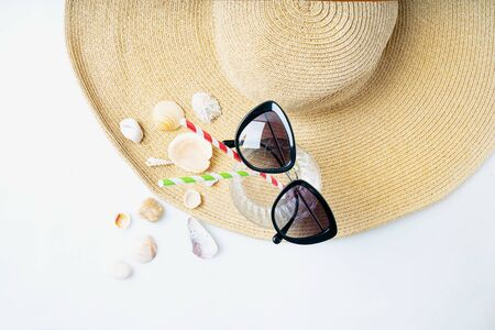 Summertime concept. Beach set: sunglasses, shells and glass with straws over summer hat on the white background. Top view.