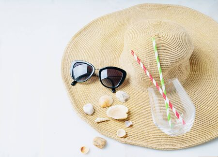Summertime concept. Beach set: sunglasses, shells and glass with straws over summer hat on the white background.