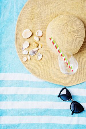 Summertime concept. Beach set: sunglasses, shells, glass with straws and summer hat on the striped beach towel. Top view.