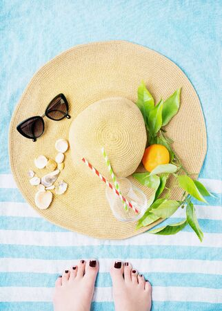 Summertime concept. Beach set: sunglasses, shells, glass with straws and branch with orange over the summer hat on the striped beach towel. Female feet on the towel. Top view.