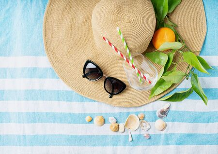 Summertime concept. Beach set: sunglasses, shells, glass with straws and branch with orange over the summer hat on the striped beach towel. Top view. Standard-Bild