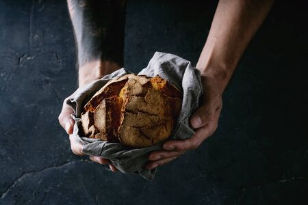 Traditional Portuguese round bread in male hands on dark background.