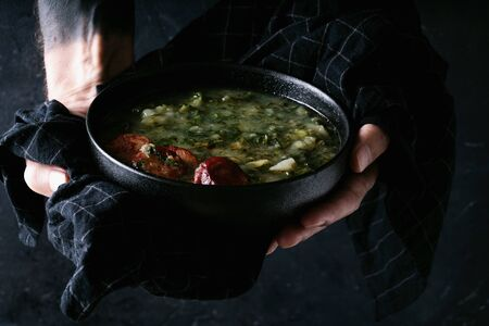 Caldo Verde Soup with greens and chopped chorizo on the top in the bowl in male hands on a dark background. Selective focus. Close up