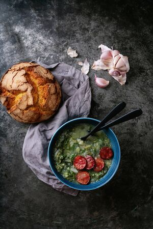 Caldo Verde Soup with greens and chopped chorizo on the top in the bowl on a dark background with traditional round bread and garlic. Top view Standard-Bild