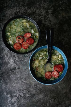 Caldo Verde Soup with greens and chopped chorizo on the top in two bowls on a dark background. Top view