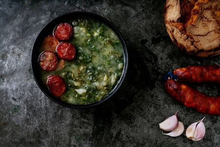 Caldo Verde Soup with greens and chopped chorizo on the top in the bowl on a dark background. Traditional round bread, chorizo and garlic. Top view. Close up