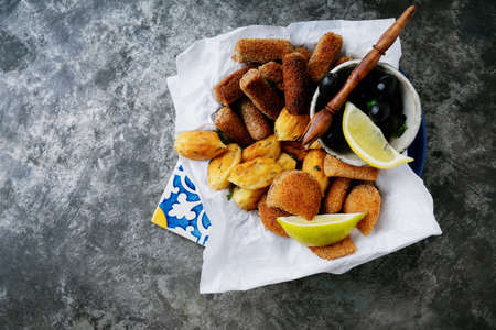 Traditional Portuguese snacks shrimp rissoles, beef croquettes and cod fish pasties on the pan served with lemon, olives and tomato sauce. Rissois de camarão, pasteis de bacalhau, croquettes de carne.