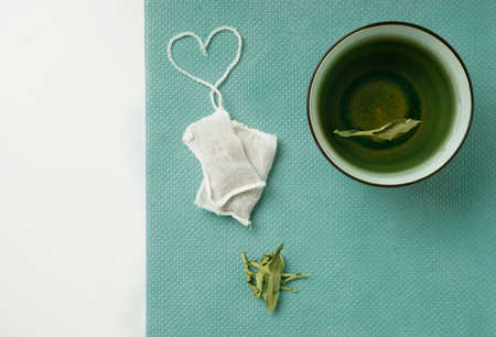 Lemon Verbena tea in  a mug and teabags with heart shaped string over a tidewater green background. Top View. Flat Lay
