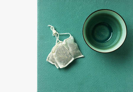 Lemon Verbena tea in teabag and empty mug  over a tidewater green background. Top View. Flat Lay