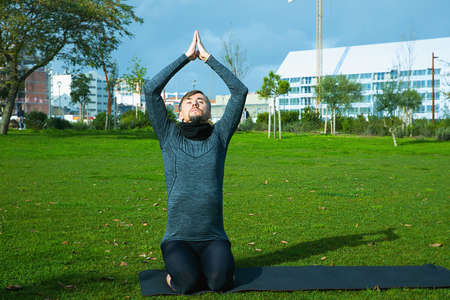 Middle aged man doing breathing, relaxation, yoga, stretching, exersice, workout in the park using yoga mat. Natural beginner yoga posing. Healthcare concept.