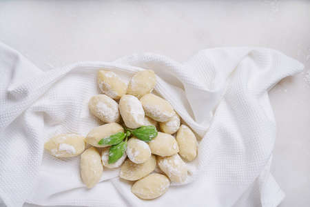 Traditional italian potato gnocci  (pasta) decorated with basil leaf. Uncooked pasta concept. Top View. Flat Lay