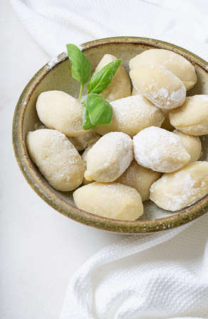 Traditional italian potato gnocci  (pasta) decorated with basil leaf, eggs, flour. Uncooked pasta concept.