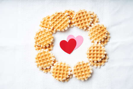 Mini waffles decorated with paper hearts over a white  textile background. St Valentine's concept. Top View. Flat Lay