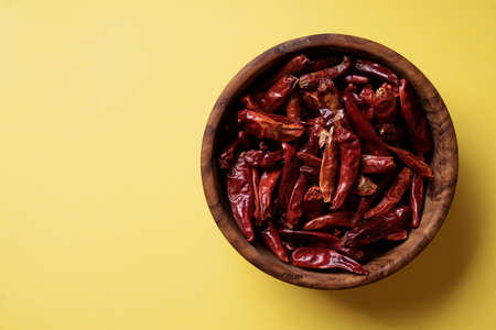 Dry chili pepper in a wooden bowl over yellow background.  Top View. Flat lay
