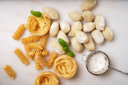 Traditional Italian pasta: Tagliatelle, fusilli and gnocchi  decorated with basil leaves over a white background.  Italian food concept. Top View. Flat Lay