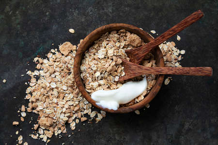 Granola, muesli in wooden bowl with wooden spoons with yogurt over a rustic metal background. Top View. Flat Lay