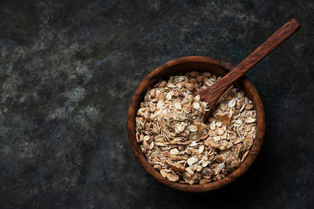 Granola, muesli in wooden bowl with wooden spoon over a rustic metal background. Top View. Flat Lay