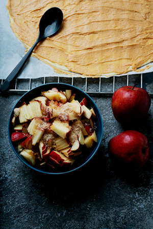Cooking process of apple swirls. Dough with spread peanut butter filling and cut apples with brown sugar and two apples. Top View. Flat lay Standard-Bild