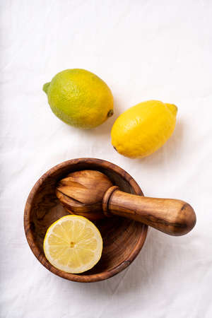 Lemons with wooden olive tree squeezer  and a bowl over a white textile background. Top View. Flat Lay.
