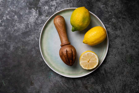 Lemons with wooden Juicer over a blue ceramic plate. Flat Lay. Top View. Copy Space Standard-Bild