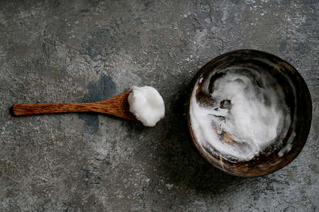 Organic coconut oil in coconut bowl with coconut spoon over rustic background. Sustainability concept. Top View. Flat Lay.