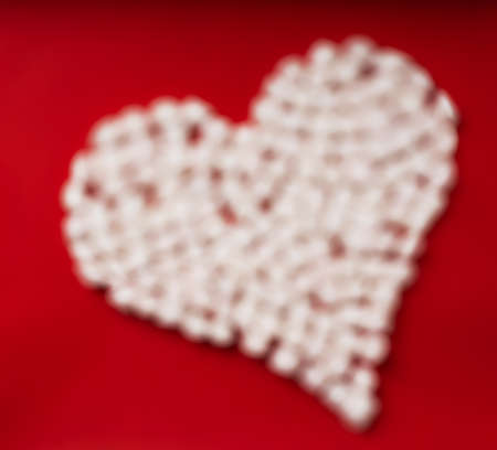 Soft Focus heart symbol made from marshmallows on red background. Top View. Flat Lay