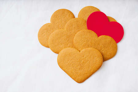 Heart shaped  gingerbread cookies with red card over a white textile background. Selective Focus. Copy space. Standard-Bild