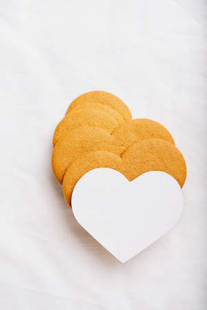 Heart shaped  gingerbread cookies  with a white card over a white textile background. Flat Lay. Top View