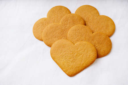 Heart shaped  gingerbread cookies  over a white textile background. Selective Focus. Copy Space. Standard-Bild