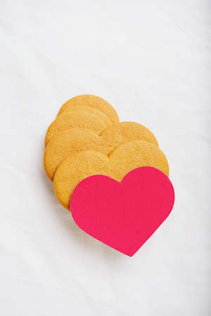 Heart shaped  gingerbread cookies with red card over a white textile background. Flat Lay. Top View