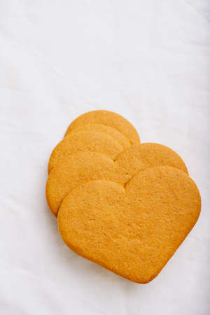 Heart shaped  gingerbread cookies  over a white textile background. Flat Lay. Top View