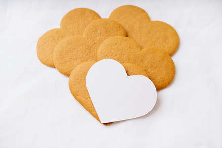 Heart shaped  gingerbread cookies  with a white card over a white textile background. Selective Focus. Copy space Standard-Bild