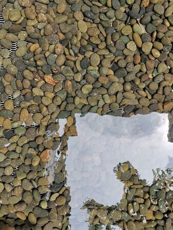 The rocks in the clear water have beautiful reflections as an art