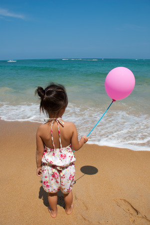 Kid with pink balloon on the beach and blue sky photo
